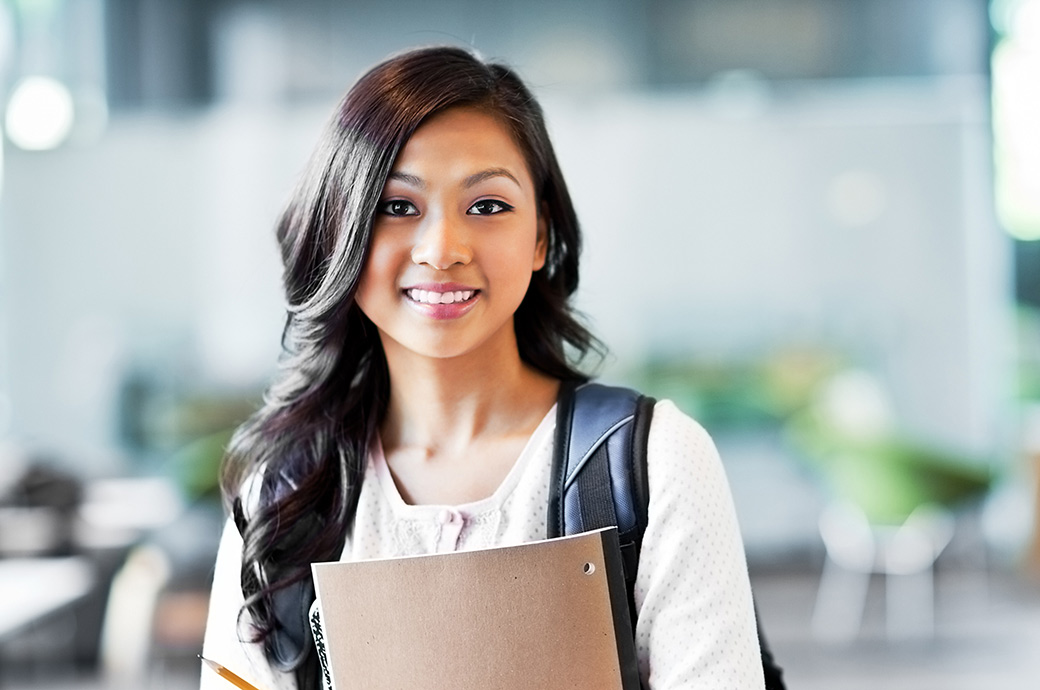 En smilende teenager iført en rygsæk bærer sine notesbøger. Hun har kontaktlinser i øjene