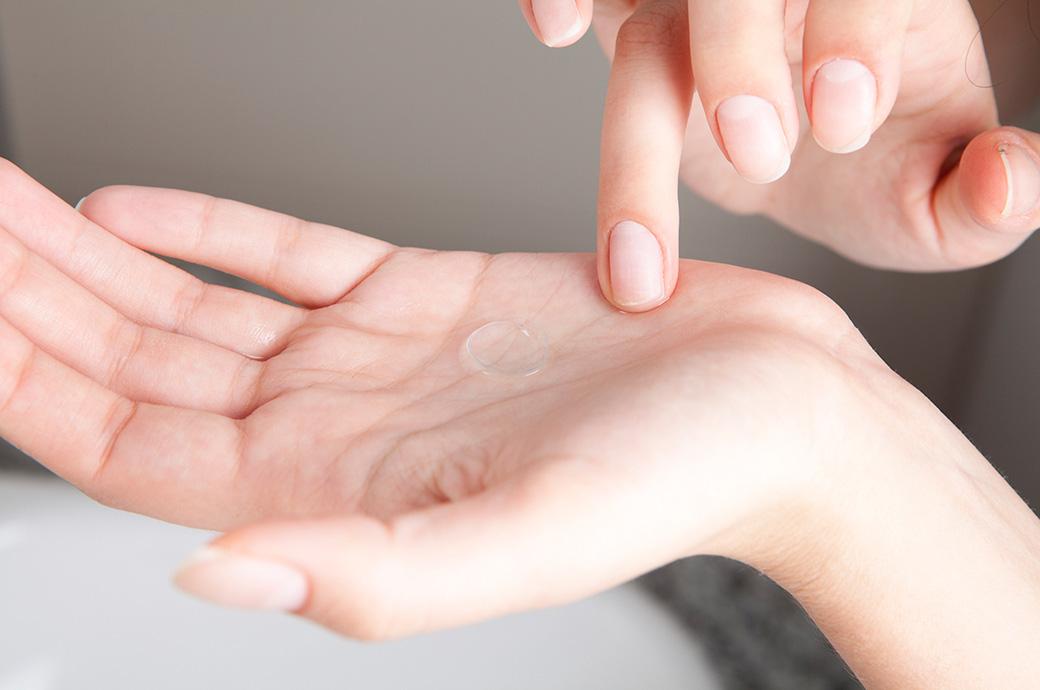 En person sidder med en kontanktlinse på sin håndflade