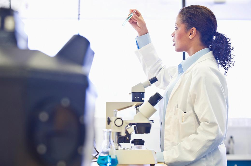 Læge kigger i et mikroskop i laboratoriet.