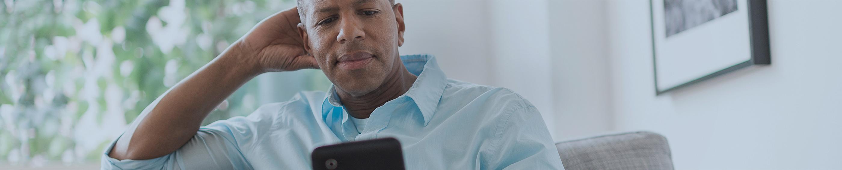 En far læser en artikel om kontaktlinser til børn på sin tablet