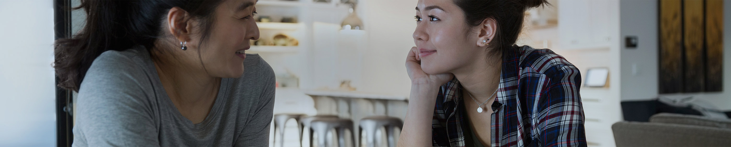 En ung kvinde, der taler med sin mor i køkkenet, hun bruger kontaktlinser