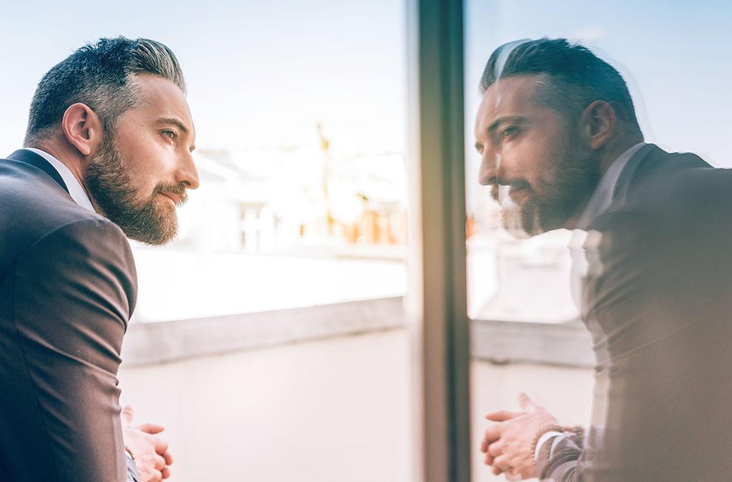 Billede af en mand, der ser på sin refleksion i et vindue