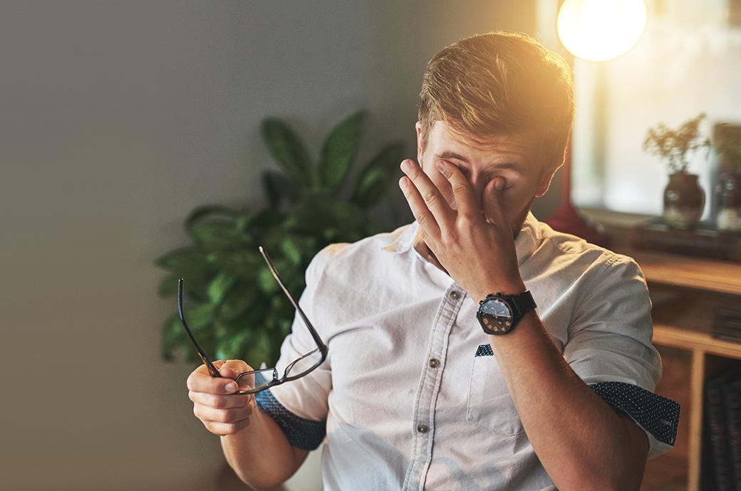 Billede af en mand der tager brillerne af for at gnide sine øjne