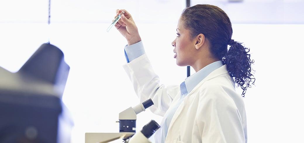 En sundhedsplejerske inspicere et reagensglas i et laboratorium