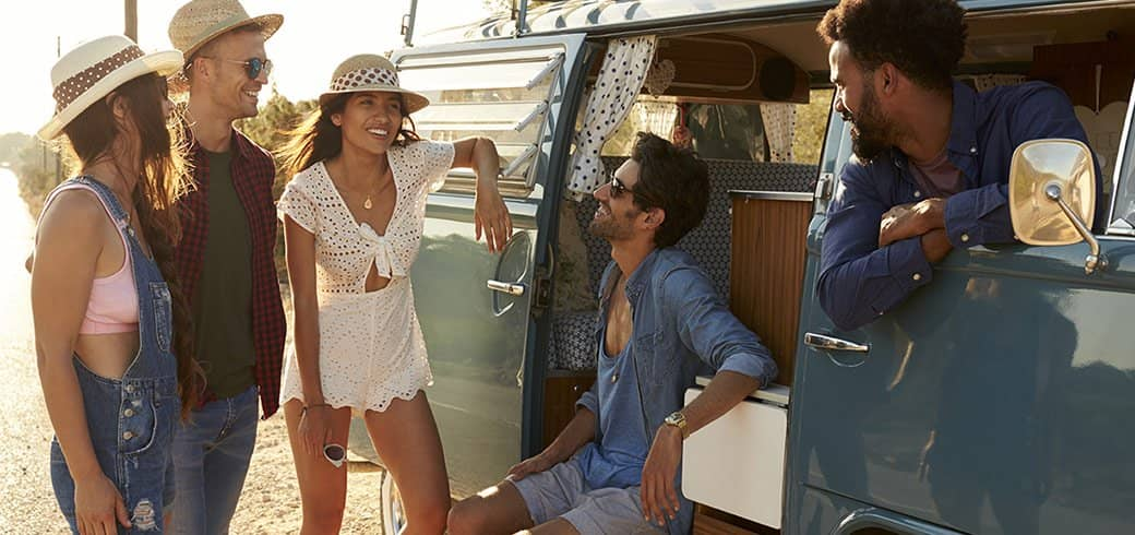 En gruppe venner der hygger sig ved deres bil i solskin