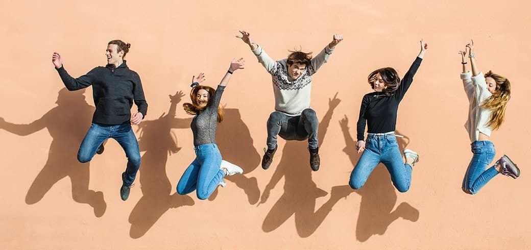 En gruppe venner hopper op i luften, griner og smiler.