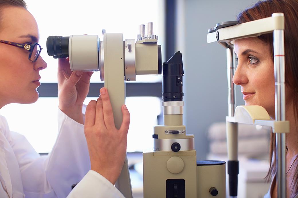 Billede set fra siden af en optiker og en ung kvinde, der kigger gennem et funduskamera