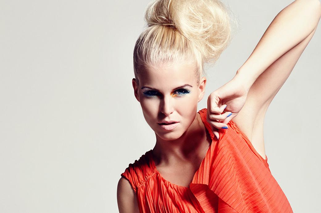 En ung, fashionabel kvinde iført kontaktlinser står med sin albue opad og ser på kameraet