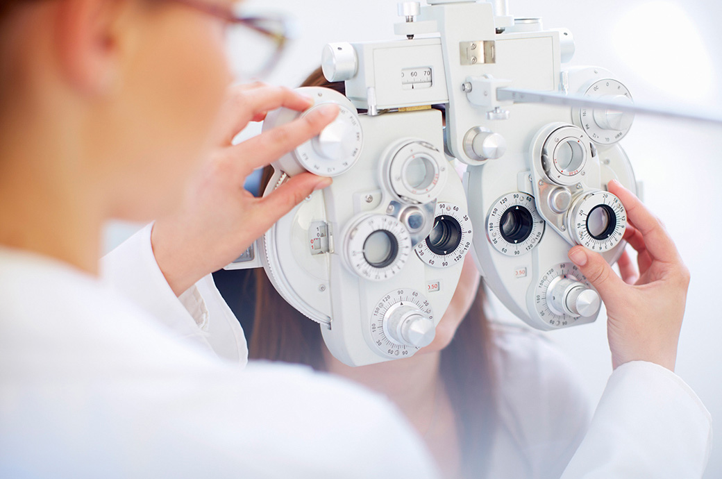 En ung kvinde bag en phoropter, mens optikeren kontrollerer hendes øjne under en synstest.