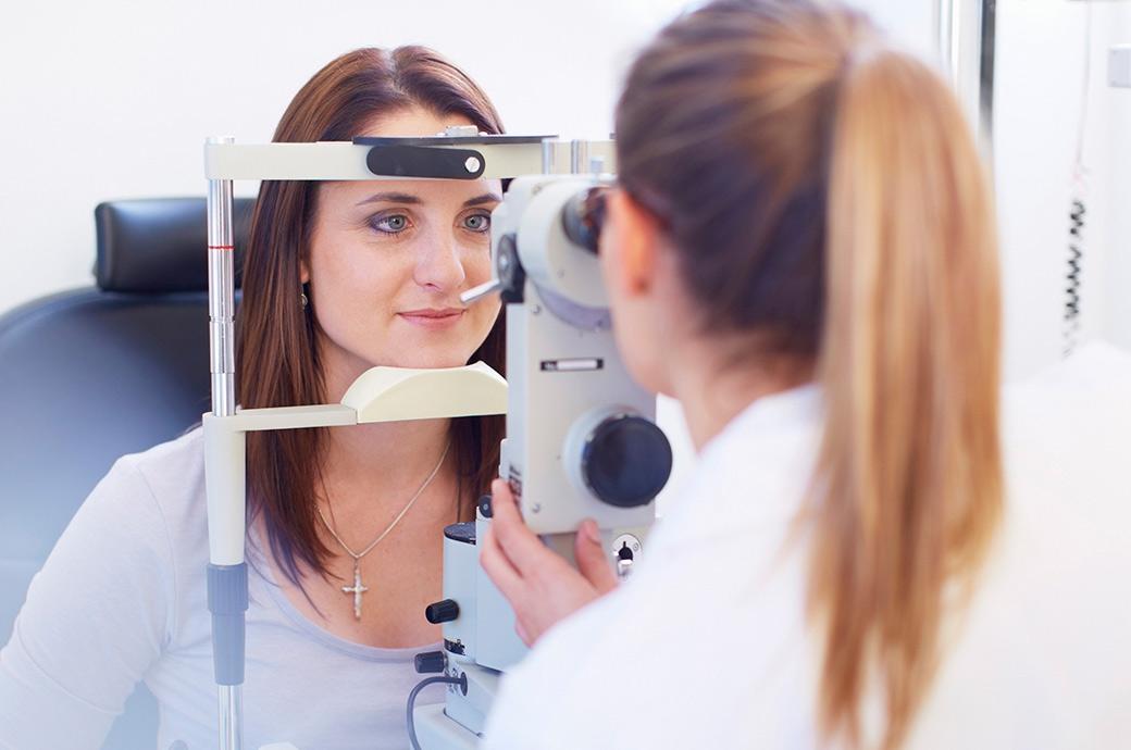 Kameraet fokuserer på en ung kvinde, der kigger gennem et funduskamera, mens hendes optiker kigger gennem det fra den anden side