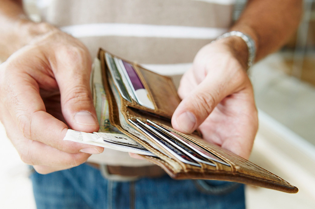 Et nærbillede af en person, der tager pengesedler ud af en tegnebog
