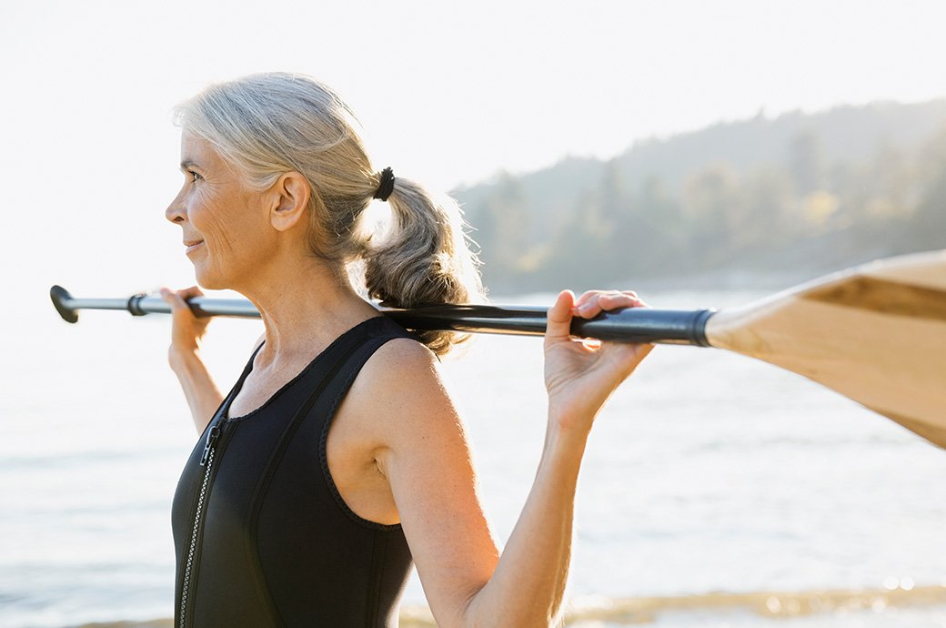 Billede af en moden kvinde udenfor med en padle