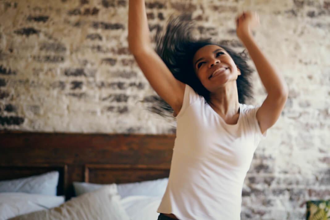 Et billede af en ung kvinde, der danser i hendes soveværelse