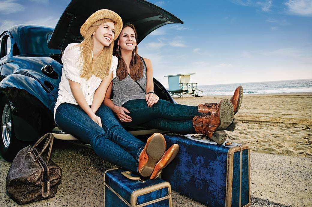 To piger med kontaktlinser, der sidder i bagagerummet af en bil ved stranden med deres bagage klar til at tage på ferie.