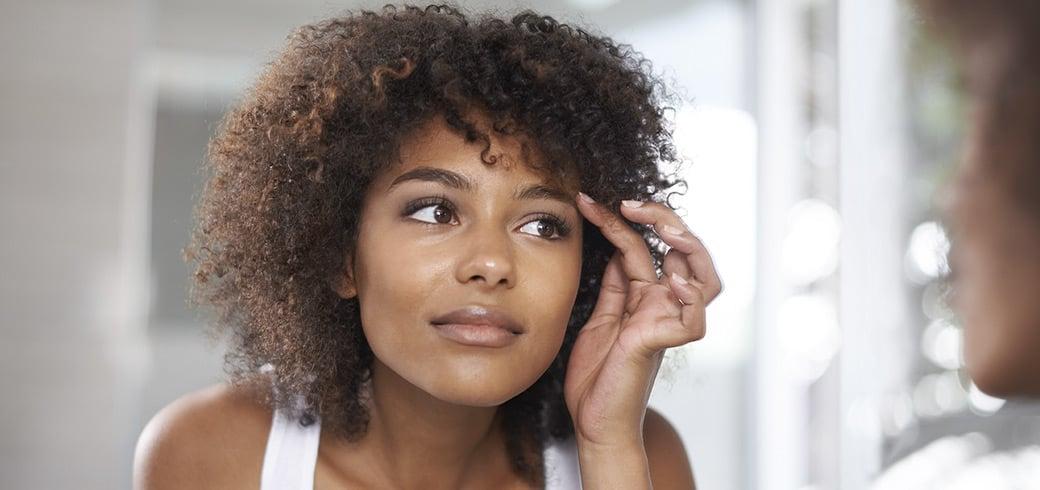 En ung kvinde kigger på sine øjne i spejlet.