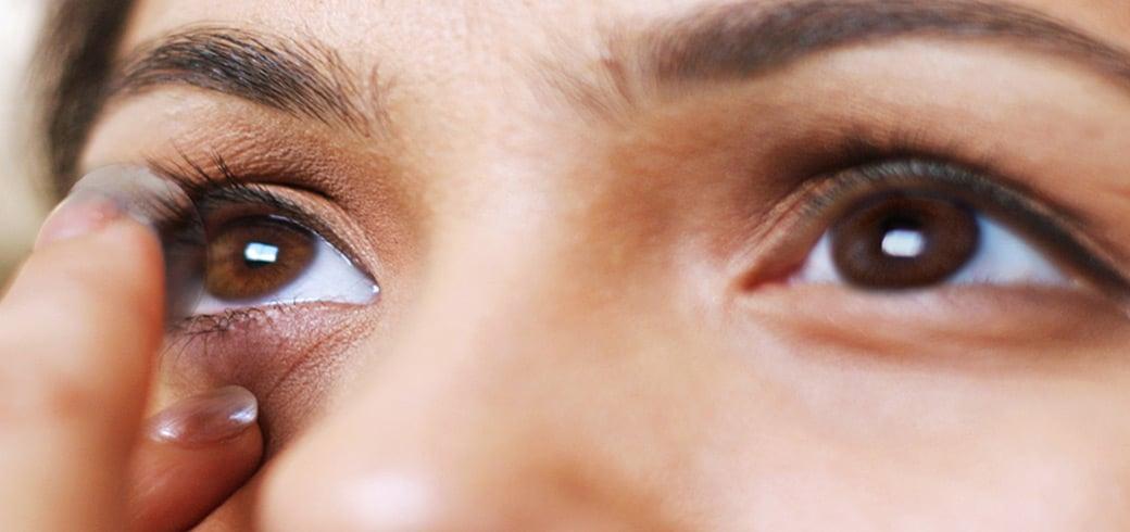 Nærbillede af en ung kvinde der kommer en kontaktlinse i øjet.